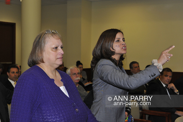 Nassau County Legislature, controlled by Republicans, votes along party lines to consolidate 8 police precincts into 4, on Monday, March 5, 2012, at Mineola, New York, USA. Milagros Vicente (right, pointing finger), a North Valley Stream resident, was one of those shouting out in audience after a Yes vote by one of the legislators. (Ann Parry/Ann Parry, ann-parry.com)
