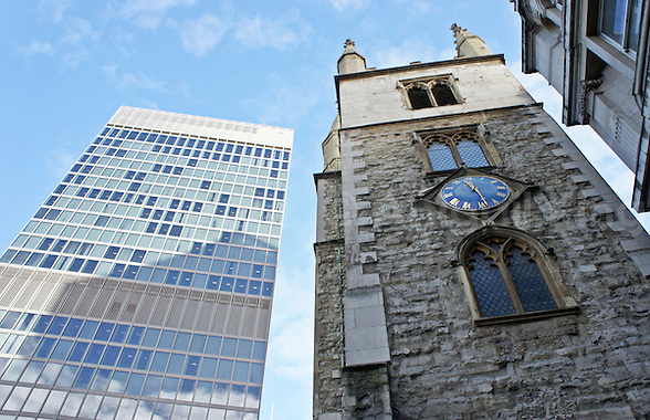 Photo of tiny St Andrew's Church among the gleaming concrete buildings of the City of London