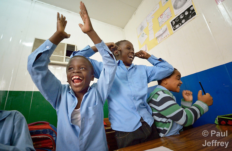 Refugee boys celebrate winning an in class competition in a school operated by St. Andrew's Refugee Services in Cairo, Egypt. Located at St. Andrews United Church of Cairo, the program is supported by Church World Service. (Paul Jeffrey)
