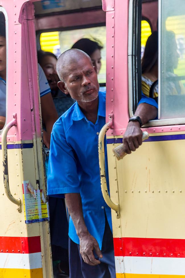 YANGON, MYANMAR - CIRCA DECEMBER 2013: Person peeking outside and looking for passengers on public bus in the city of Yangon in Myanmar (Daniel Korzeniewski)