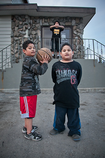 Fourteen year old, Tai Lolofietele, forms a basket with his arms for brothers Jericoh and Jerome, outside the Alaska Nazarene Church at 13th and E Street, Anchorage (Clark James Mishler)
