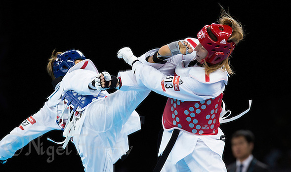 10 AUG 2012 - LONDON, GBR - Franka Anic (SLO) (right) of Slovenia blocks a kick from Gulnafis Aitmukhambetova of Kazakhstan during their women's -67kg category preliminary round contest at the London 2012 Olympic Games Taekwondo at Excel in London, Great Britain (PHOTO (C) 2012 NIGEL FARROW) (NIGEL FARROW/(C) 2012 NIGEL FARROW)
