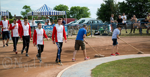 11 JUL 2015 - IPSWICH, GBR - Ian Johnson (second from the right) and Reece Johnson (right) prepare the track for the start of the Celtic Cup as Paul Heard leads the England team onto the centre green to receive their  medals after winning the cycle speedway Home International at Whitton Sports and Community Centre in Ipswich, Suffolk, Great Britain (PHOTO COPYRIGHT © 2015 NIGEL FARROW, ALL RIGHTS RESERVED) (NIGEL FARROW/COPYRIGHT © 2015 NIGEL FARROW : www.nigelfarrow.com)