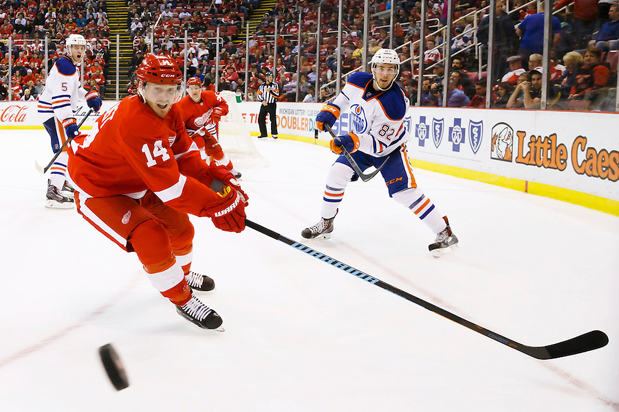 Mar 9, 2015; Detroit, MI, USA; Edmonton Oilers defenseman Jordan Oesterle (82) passes the puck past Detroit Red Wings center Gustav Nyquist (14) in the third period at Joe Louis Arena. Detroit won 5-2. Mandatory Credit: Rick Osentoski-USA TODAY Sports (Rick Osentoski/Rick Osentoski-USA TODAY Sports)