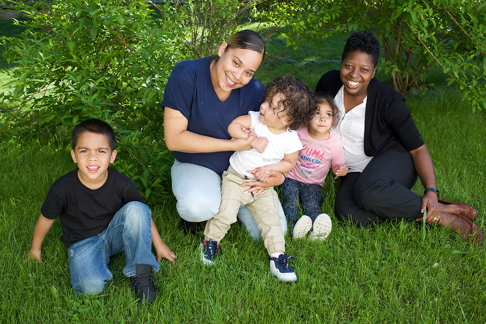 Supportive Housing program case worker, Melissa (in white shirt) with her client Irma and three of Irma's four children: Joels, age 5, Delicia, age 3 and Julio, age 18 months. Melissa has provided support to Irma for over two years. Irma, age 24, left home at the age of nine after she and her brother suffered abuse at the hands of their step father. After several years in the care of foster homes and living homeless, Irma became pregnant at age 15. By the age of 23, Irma had lived through periods of homelessness and had become mother to four children with two different men, both of whom were abusive. Six months into her fourth pregnancy, Irma's partner threw her down the stairs and she went into premature labour. Medical staff told Irma that she would miscarry but her youngest son, Julio survived after spending the first six months of his life in hospital. The sustained involvement of medical professionals in Irma's life alerted the Supportive Housing program to her situation. Case worker Melissa began working with Irma, offering support, advice and providing the funds to purchase items for the care of baby Julio. Melissa made representations to the Department of Children and Families (DCF) to vouch for Irma's character and convince them that Irma should not be separated from her children. Melissa encouraged Irma to go back to school and complete her high school diploma. Supportive Housing provided Irma a housing-voucher so that she could keep her children and live independently of her abusive partner. Irma now lives with her children who have rooms of their own and a back yard in which to play. Julio, now eighteen months, has significant health needs but the relative stability of Irma's life now means she can look to the future with a sense of optimism. She hopes to complete her associates degree in nursing and eventually earn an income that will allow her to live in accommodation without the need of a subsidy from Supportive Housing. (Tom Pietrasik)