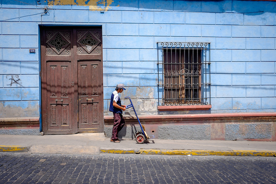 AREQUIPA, PERU - CIRCA APRIL 2014: Man walking with hand cart on typical street of Arequipa. Arequipa is the Second city of Perú by population with 861,145 inhabitants and is the second most industrialized and commercial city of Peru. (Daniel Korzeniewski)