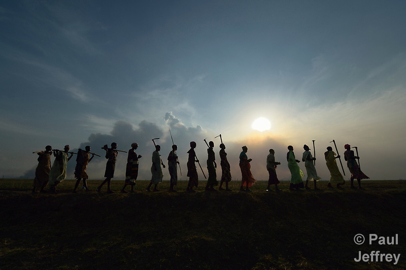 After working together in a community garden, women sing and dance as they walk home on April 12, 2017, atop a dyke they constructed to control flooding around Dong Boma, a Dinka village in South Sudan's Jonglei State. Most of the women's families recently returned home after being displaced by rebel soldiers in December, 2013, and they face serious challenges in rebuilding their village while simultaneously coping with a drought which has devastated their cattle herds. The Lutheran World Federation, a member of the ACT Alliance, is helping villagers restart their lives with support for housing, livelihood, and food security. (Paul Jeffrey)
