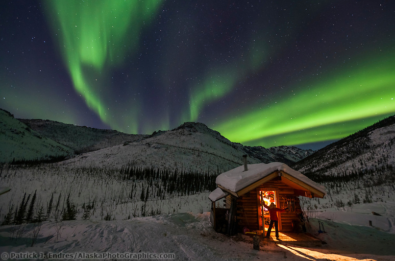 Visitors to the Caribou bluff cabin in the White Mountains National Recreation area view the northern lights overhead on a winter night. (Patrick J. Endres / AlaskaPhotoGraphics.com)