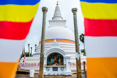 Thuparama Dagoba and the Buddhist flag, Ancient City of Anuradhapura, Sri Lanka, Asia. This is a photo of Thuparama Dagoba and the Buddhist flag in The Ancient City of Anuradhapura in the 'cultural triangle' area of Sri Lanka, Asia. Thuparama Dagoba is the oldest Dagoba in the Ancient City of Anuradhapura, and also Sri Lanka