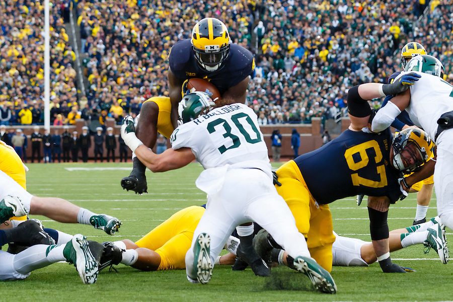 Oct 17, 2015; Ann Arbor, MI, USA; Michigan Wolverines running back De'Veon Smith (4) is stopped short of the end zone by Michigan State Spartans linebacker Riley Bullough (30) at Michigan Stadium. Mandatory Credit: Rick Osentoski-USA TODAY Sports (Rick Osentoski/Rick Osentoski-USA TODAY Sports)