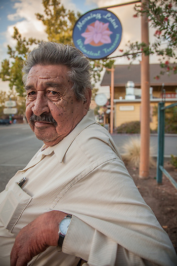 """Retired field worker Ramiro """"Ray"""" Espinoza on a park bench in downtown Calistoga.  """"I have worked all over Sanoma and Napa Counties...I have picked all kinds of fruits and vegetables and I ended up here in Calistoga."""" (© Clark James Mishler)"""