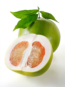 Fresh Pomelo grapefruit whole and cut with leaves (by food photographer Paul Williams. http://www.funkyfood.co.uk)