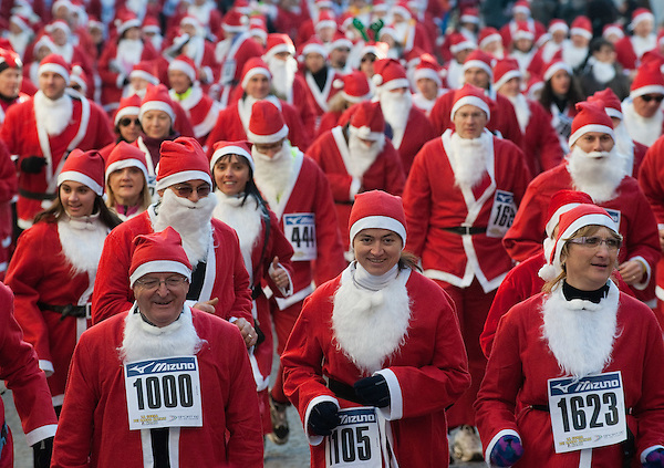 NOALE, ITALY - DECEMBER 18:  Participants dressed as Father Christmas take part in the Noale Sant Run on December 18, 2011 in Noale, Italy. Close to two thousand people participated in the third annual Noale Santa Run, one of the largest non competitive Santa Run in Italy. (Marco Secchi)