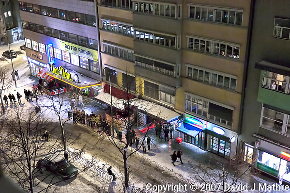 Line of folks waiting for a taxi outside a club in Oslo. Image taken with a Nikon D2xs camera and 28-70 mm f/2.8 lens (ISO 1600, 70 mm, f/2.8, 1/20 sec). Image processed with Capture One Pro and NIK Define. (David J Mathre)