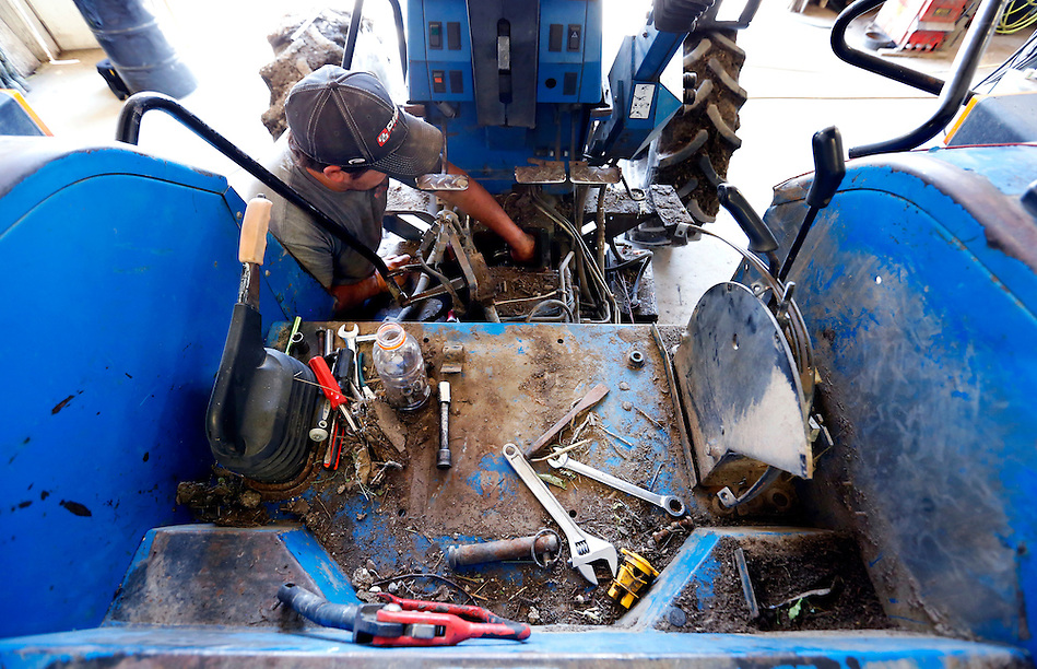 Farm mechanic Jordan Dammann works to repair a tractor in the workshop on the Dammann Farm in rural Page County on July 10, 2014. (Christopher Gannon/The Register)