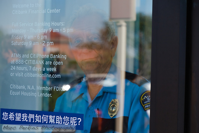 Charles, a security guard at a Citibank in Irvine, CA, warily watches through a locked door as protesters from the Occupy Orange County, Irvine camp march in front of his bank. (Marc C. Perkins)