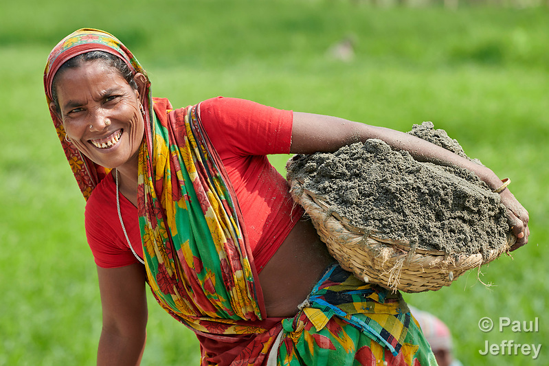 In order to raise her home a few inches, Komela Khatun carries dirt in a basket in West Fasura, a village on an island in the Brahmaputra River in northern Bangladesh. Severe flooding in August 2017 destroyed the island's crops but RDRS Bangladesh, a member of the ACT Alliance, provided emergency cash grants to vulnerable island families so they could reestablish their household economies and restart their lives. (Paul Jeffrey)