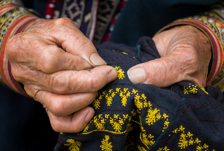 SAPA, VIETNAM - CIRCA SEPTEMBER 2014:  Detail of hands of old Red Dao woman knitting in Ta Phin Village near Sapa, North Vietnam. (Daniel Korzeniewski)