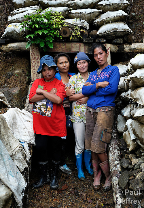 Women gold miners in the Diwalwal area on the Philippines' southern island of Mindanao. They and other small scale mining families are fighting back against plans to displace them by the Philippine Mining Development Corporation, a front company for foreign mining companies that seeks to install a large-scale open pit gold mine in the area, also known as Mt. Diwata. The small miners were given notice to evacuate the area by June 5, 2012, or risk being forcibly removed by the military. The miners have defiantly refused to leave, and formed a formal association to demand respect for their rights in the Philippines courts. .