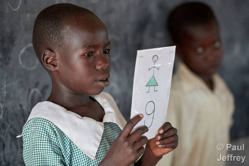 "A girl holds a sign for the letter ""G"" during a class in the Catholic Church-sponsored St. Daniel Comboni Primary School in Lugi, a village in the Nuba Mountains of Sudan. The area is controlled by the Sudan People's Liberation Movement-North, and frequently attacked by the military of Sudan. The church has sponsored schools and health care facilities throughout the war-torn region. (Paul Jeffrey)"