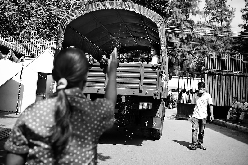 A woman throws rice in offering as a government truck carrying the body of one victim and her family depart for their hometown of Kampong Chom, several hours from Phnom Penh, Cambodia. Several hundred perished in a stampede tragedy when an unknown event sparked panic and thousands attempted to flee Diamond Island in the middle of the Mekong River over the bridge connecting it to the river bank. (Quinn Ryan Mattingly)