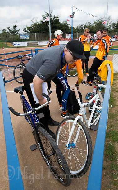 13 SEP 2014 - IPSWICH, GBR - Referee Steve Copping checks bikes before the start of the 2014 British Open Club Cycle Speedway Championships at Whitton Sports & Community Centre in Ipswich, Great Britain (PHOTO COPYRIGHT © 2014 NIGEL FARROW, ALL RIGHTS RESERVED) (NIGEL FARROW/COPYRIGHT © 2014 NIGEL FARROW : www.nigelfarrow.com)