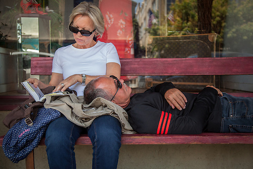 Prior to continuing their motorcycle venture back to San Francisco Michael Ajaz, of Stuttgart, Germany, takes a nap on the lap of his wife, Gudran Baumgart, in downtown Calistoga (Clark James Mishler)