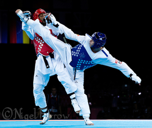 10 AUG 2012 - LONDON, GBR - Lutalo Muhammad (GBR) (left) of Great Britain blocks a kick from Nicolas Garcia Hemme (ESP) (right) of Spain during their men's -80kg category quarter final contest at the London 2012 Olympic Games Taekwondo at Excel in London, Great Britain (PHOTO (C) 2012 NIGEL FARROW) (NIGEL FARROW/(C) 2012 NIGEL FARROW)