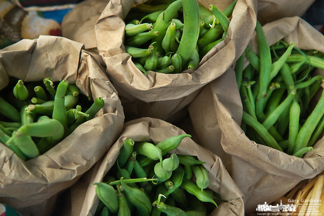 Green beans in brown paper bags for sale at farmer's market (Gary Gardiner/SmallTown Stock)