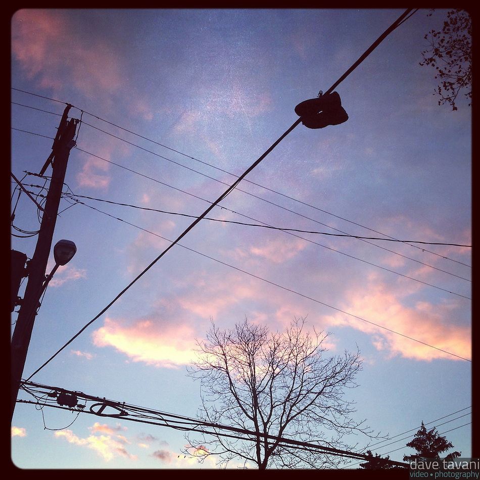 A pair of shoes dangle on a wire silhouetted by the last light of the day on Cherokee Street in the Germantown section of Philadelphia on November 24, 2012. (Dave Tavani)