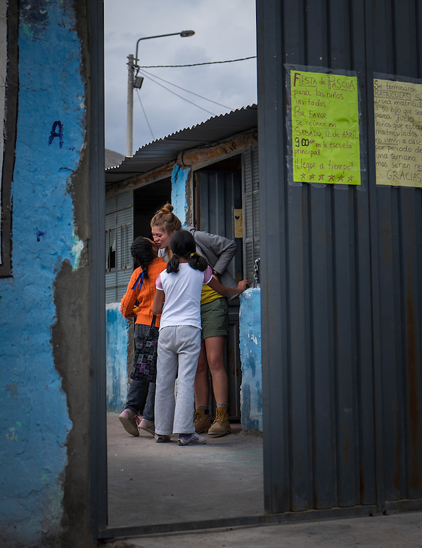 AREQUIPA, PERU - APRIL 7, 2014: Volunteer teacher welcoming student in the community of Flora Tristan for HOOP Peru. HOOP Peru is a NGO fully committed to breaking the cycle of poverty by empowering the Flora Tristan families through enhancing their education. (Daniel Korzeniewski)