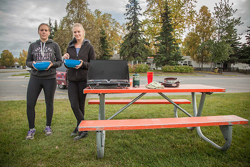 "German travelers Melissa and Lisa are about to eat after preparing dinner on the Delaney Park Strip in Anchorage.  ""We started in Canada and plan to drive all over Alaska, back through Canada, California, Mexico, and Central America."" (© Clark James Mishler)"