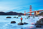 A man stands on a rock at Marshall's Beach admiring the Golden Gate Bridge in San Francisco, California. (Seth K Hughes)