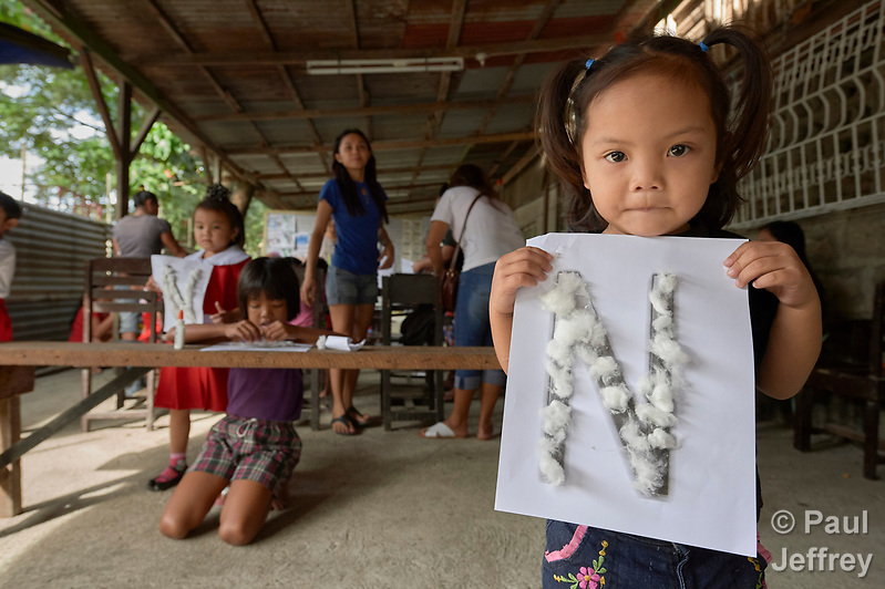 A girl shows off her class work--the letter N covered with glued-on cotton balls--in a preschool sponsored by the Kapatiran-Kaunlaran Foundation (KKFI) in Pulilan, a village in Bulacan, Philippines. KKFI is supported by United Methodist Women. (Paul Jeffrey)