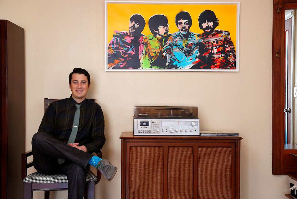 Nick Van Berkum, a communications specialist in sociology at Iowa State, sits with his hand-cut Beatles stencil and a record player stereo in his Ames home. Nick's art ranges from his stenciled work to event posters for bands to spray painted art and beyond. He often listens to his record collection while creating his artwork. (photo by Christopher Gannon) (Christopher Gannon)