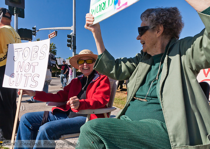 Cov (left) and Virginia (right) sit in lawn chairs while holding signs at the Occupy Orange County, Irvine camp on November 5. (Marc C. Perkins)