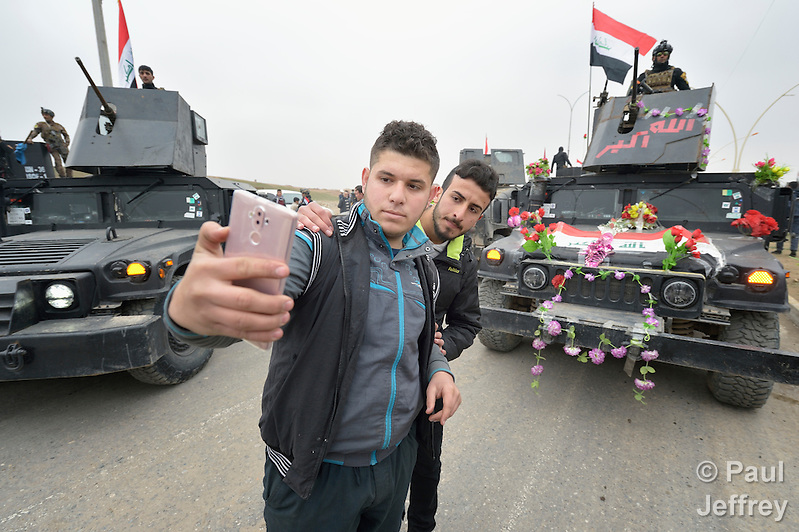 Two residents of Mosul celebrate the partial liberation of their city from control by the Islamic State group by taking a selfie on January 27, 2017, in front of festooned army vehicles. Although a portion of the city has been liberated from ISIS, fierce fighting is predicted as the army moves to retake the remainder of the city. (Paul Jeffrey)