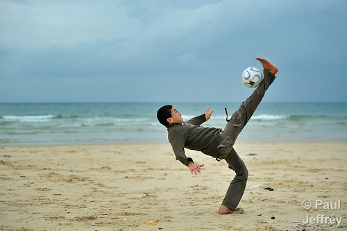 A boy kicks the ball over his head as children play football along the beach in Gaza. Although the Palestinian territory fronts the sea, Gazans are not allowed to venture more than two kilometers from shore without coming under fire from Israeli gunboats..