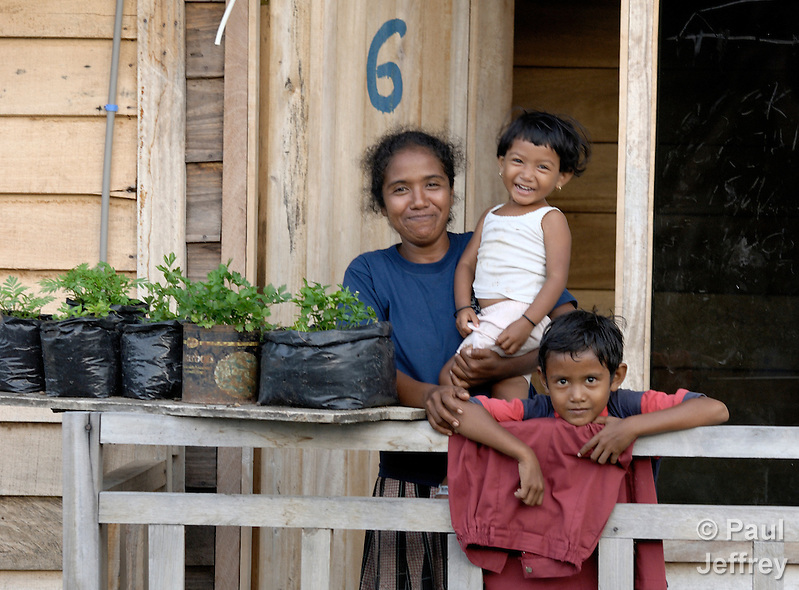 In this 2007 photo, Rusmiati and her two children at her home in Lhok Me, in Indonesia's Aceh province. Rusmiati was left homeless by the 2004 tsunami, but YEU, a member of the ACT Alliance, worked with the village to build new houses in a safer area, as well as help revitalize their income generating activities. Her children are Fathan, 3, and Rahmat, 8. The tsunami killed 221,000 people in Aceh province and left more than 500,000 displaced. Compare this photo with 2014 image of her in same spot with these two children and one more born in th interim. In Blang Ulam, Aceh, survivors of the 2004 tsunami are living in new homes constructed by CD Bethesda/YAKKUM Emergency Unit and the ACT Alliance. (Paul Jeffrey)
