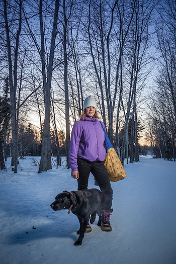 """Anchorage School District Speach and Language Pathologist Meliss Janigo with her dog Lilly on the Tony Knowles Coastal Trail near Westchester Lagoon.  majanigo@gmail.com  """"What's in the bag?""""  """"Ice skates…I was skating on Westchester Lagoon…perhaps it was because of the football game…but the lagoon was completely empty…we skated laps…it was wonderful."""" (© Clark James Mishler)"""
