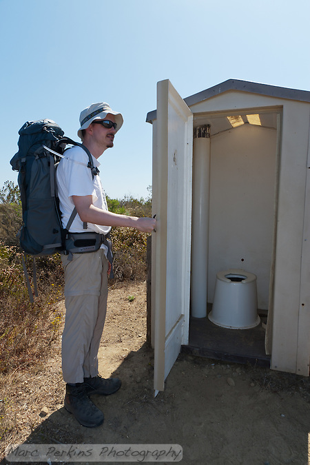My friend holds open the door to the pit toilet so you, my kind readers, can see what it's like.  Clean, low-smell, and when we were there stocked with toilet paper.  Note: this photograph has had an element unrelated to the subject of the photograph (documentation of the condition of the toilet) removed in Photoshop. (Marc C. Perkins)