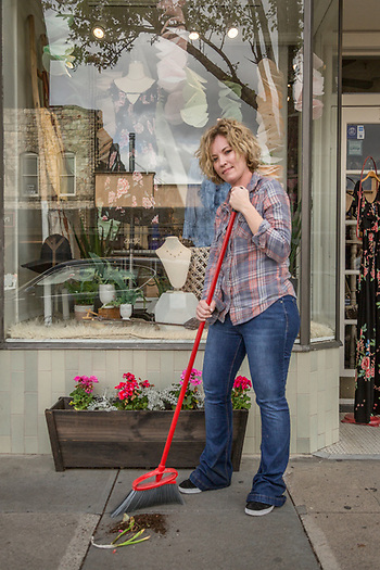 Rove co-owner Jessica Maas cleans up after planting geraniums outside her store on Lincoln Avenue in Calistoga. (Clark James Mishler)
