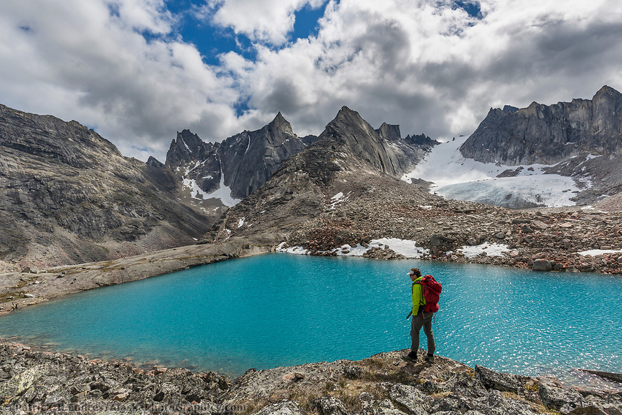 Alaska tourism photos: Man pauses while hiking at the edge of a blue lake in the Arrigetch Peaks, Valley of Aquarius, Gates of the Arctic National Park, Alaska (Patrick J Endres / AlaskaPhotoGraphics.com)