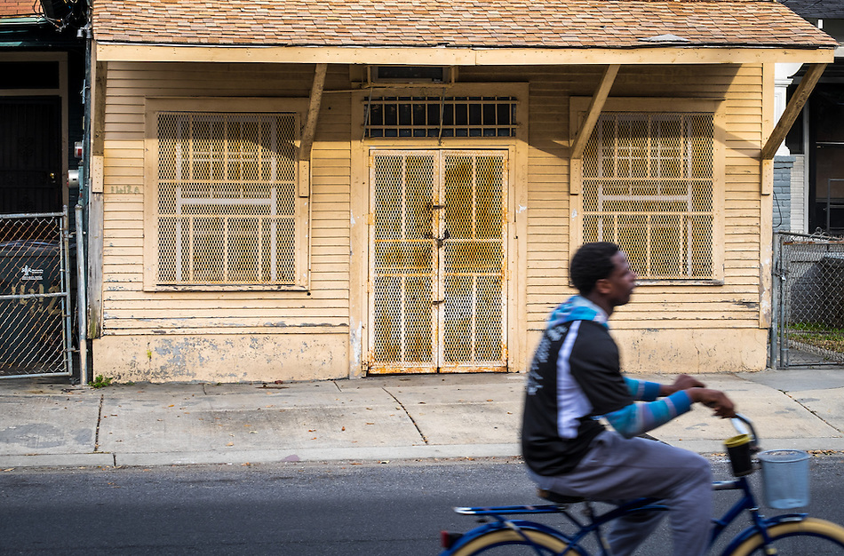 NEW ORLEANS - CIRCA FEBRUARY 2014: Young man riding a bicycle in the streets of McDonough, a popular community within the city of New Orleans in Louisiana. (Daniel Korzeniewski)