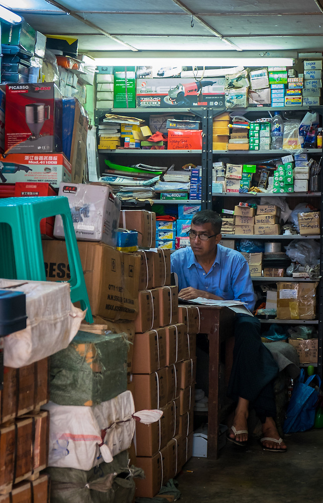 YANGON, MYANMAR - CIRCA DECEMBER 2013: Man looking at camera from a a hardware store in the streets of Yangon. (Daniel Korzeniewski)