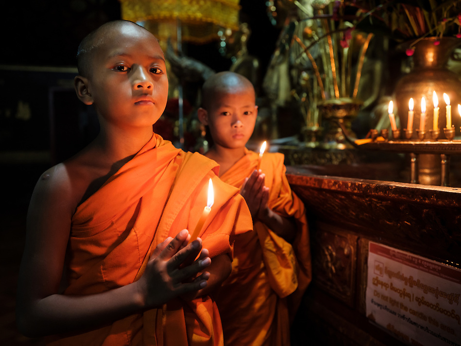 KYAING TONG, MYANMAR - CIRCA DECEMBER 2017: Monks at the Wat Jong Kham Monastery with candles looking at camera. (Daniel Korzeniewski)