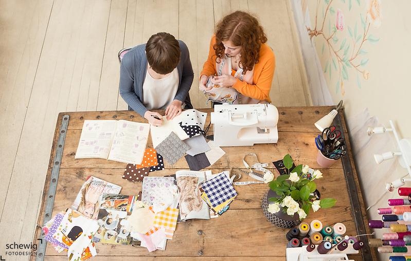 Zwei junge Frauen am Arbeitstisch ihres Workshops, Wien, Österreich, Jungunternehmerinnen im Kreativbereich, Mode oder Trend DIY als bewusste Freizeitgestaltung, Vogelperspektive (Dieter Schewig)