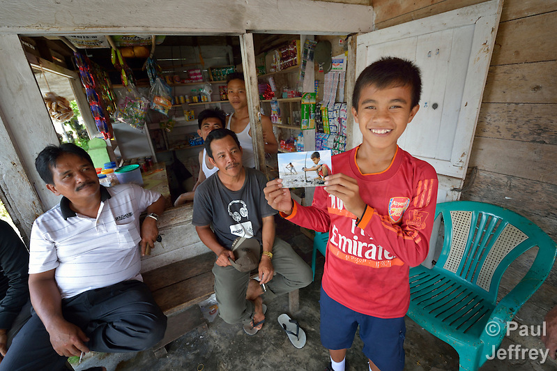 In 2014, Jefrin Zendrato, now 13, holds a photo of himself planting mangrove seedlngs in 2007 near his village of Moawo on the Indonesian island of Nias. The mangrove planting was part of assistance provided to the village by YEU, a member of the ACT Alliance, following a devastating 2004 tsunami and 2005 earthquake. His family's house was flattened by the waves, and after months of living in temporary shelters on nearby hillsides, he and his family moved into one of 72 new homes constructed in the village by YEU. With foundations of cement, they are more resilient than the pre-tsunami houses which were built entirely of wood. YEU also helped the community members restart their local economy, including the replanting of mangroves to protect the shoreline and revitalize their fishing industry.  (Parental consent obtained.) (Paul Jeffrey)
