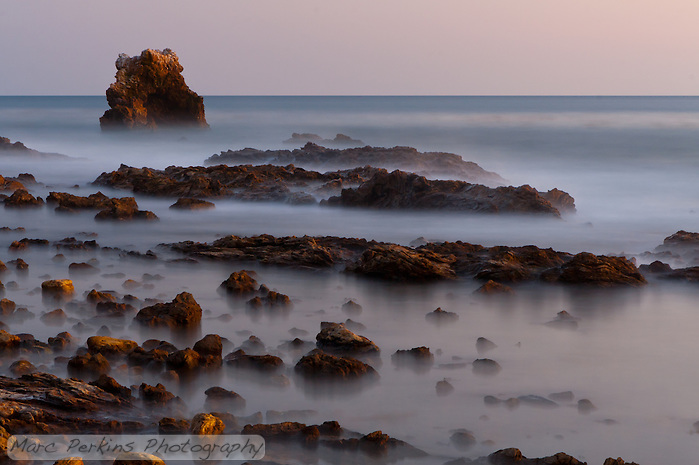 A long-exposure shot taken after sunset at Little Corona beach in Corona Del Mar (Newport Beach), CA, aiming at the distinctive arch rock off shore.  This was a two minute exposure, so the rocks were alternately covered and uncovered by water, giving them a ghostly feel, as though a low mist was over the ground. (Marc C. Perkins)