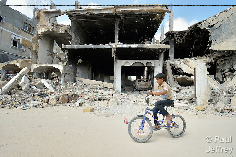 An 11-year old boy rides his bike amid the ruins of Khan Yunis, Gaza. Houses in the area were destroyed by Israeli air strikes during the 2014 war between the state of Israel and the Hamas government of Gaza. (Paul Jeffrey)